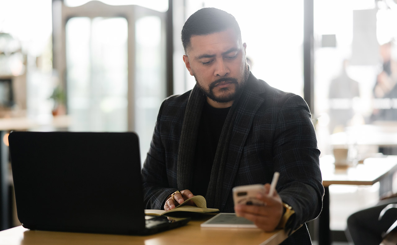 Pacific Island businessman working, getting lead alerts on his phone